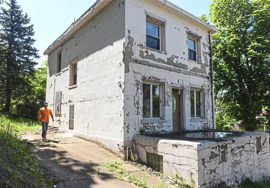 Man walks around old house with lead paint